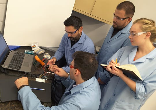 New Mexico State University associate professor Douglas Cortes, left, and his research assistants, Russell Buehling, bottom, a senior in electrical engineering; Cyrena Ridgeway, right, a master's student in civil engineering; and Salvador Ibarra, top, a senior in electrical engineering, gather around to test a flow sensor using an Arduino microcontroller.