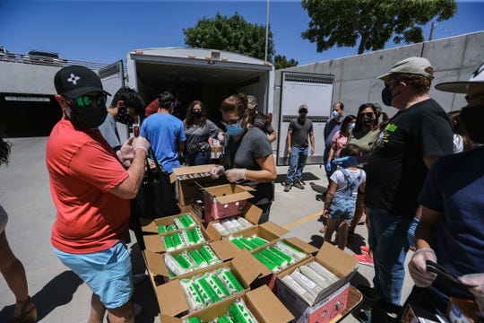 Volunteers hand out care packages full of food and toiletries at the Las Cruces City Hall on Saturday, April 25, 2020.