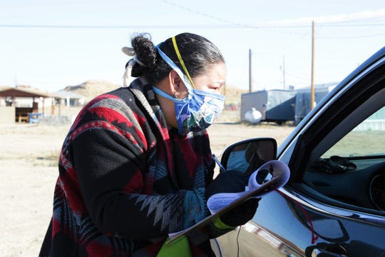 Delegate Amber Kanazbah Crotty helps a resident complete the form to receive food and other essential items from the Tooh Haltsooí Chapter on April 24 in Sheep Springs. Crotty represents the chapter on the Navajo Nation Council.