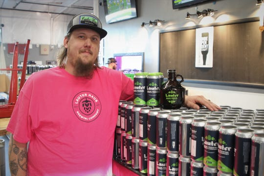 Lauter Haus Brewing Co. owner Brandon Beard displays the new 16-ounce cans and 32-ounce growlers his brewery is using to fill take-out orders for customers.