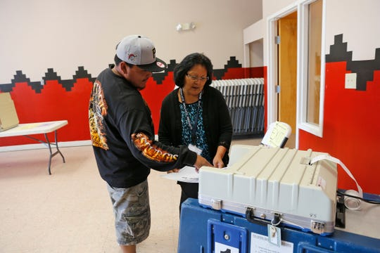 Voter Hosteen Valencia, left, is assisted by election official Renae Bennett as he casts his ballot in the Navajo Nation primary election on Aug. 30, 2016 at the Tsé Daa K'aan Chapter house in Hogback.