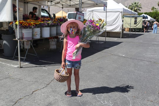 Aubrey Roberts holds some flowers she got with her mother Johanna Roberts at the Certified Farmers' Market in Palm Springs, April 25, 2020.
