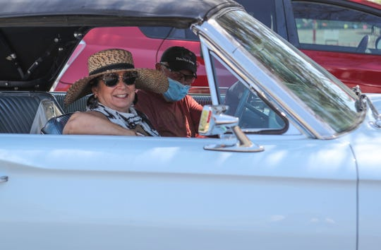 A couple leaves the Certified Farmers' Market after shopping in Palm Springs, April 25, 2020.