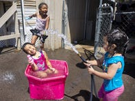 Briana Brown, 6, left, plays with her stepsisters, Maxine Portillo, 5, center, and Eileen Portillo, 2,  outside their Phoenix home on April 25, 2020.