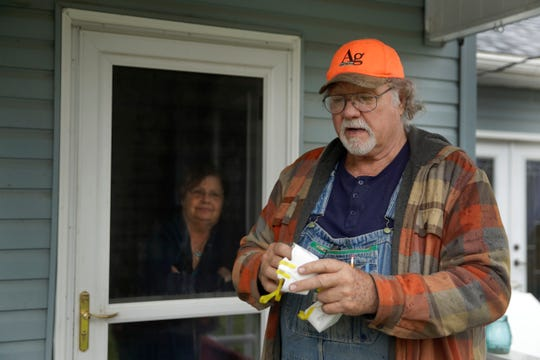 Dennis holds two of his remaining N95 masks as he stands with his wife, Sharon, at their home near Troy, Kansas, on Friday, April 24, 2020. Dennis, a retired farmer, shipped one of the couple's five masks left over from his farming days to New York Gov. Andrew Cuomo for use by a doctor or a nurse.