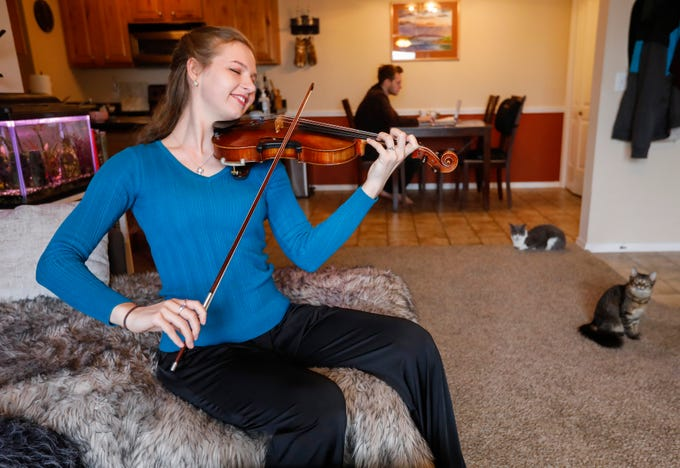 Karolina Fraczak, assistant principal of 2nd violins with the Springfield Symphony Orchestra, plays the violin in her apartment as her fiance Nate Van Devender works on his computer on Saturday, April 25, 2020. The musicians in the orchestra haven't been able to perform any concerts due to the coronavirus pandemic.