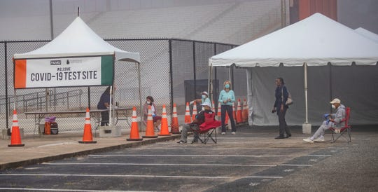 People socially distance themselves in their personal lawn chairs as they wait for the walk-up testing site in Bragg Memorial Stadium to open on Saturday, April 25, 2020.