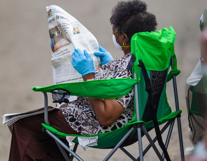 A woman wearing gloves and a mask rests in her personal lawn chair as she reads the Tallahassee Democrat while waiting to be tested for COVID-19 at the walk-up testing site at Bragg Memorial Stadium opened Saturday, April 25, 2020.