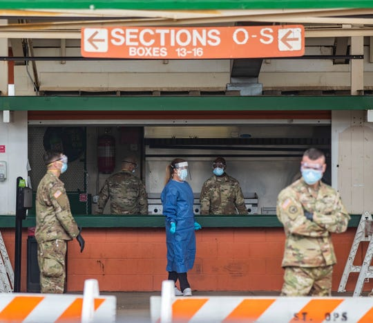 A healthcare professional and members of the National Guard wait for a person who is showing symptoms of COVID-19 to arrive to be tested at a concession stand inside Bragg Memorial Stadium Saturday, April 25, 2020.
