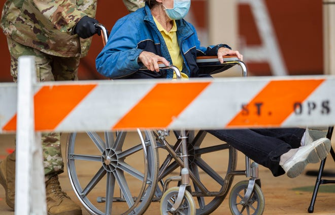 A person wearing a mask while sitting in a wheelchair is escorted out of Bragg Memorial Stadium by a member of the National Guard after being tested for COVID-19 Saturday, April 25, 2020.