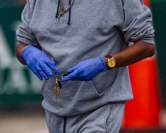 A man wearing gloves goes to his car to grab tissues before he is tested for COVID-19 at the walk-up testing site at Bragg Memorial Stadium Saturday, April 25, 2020.