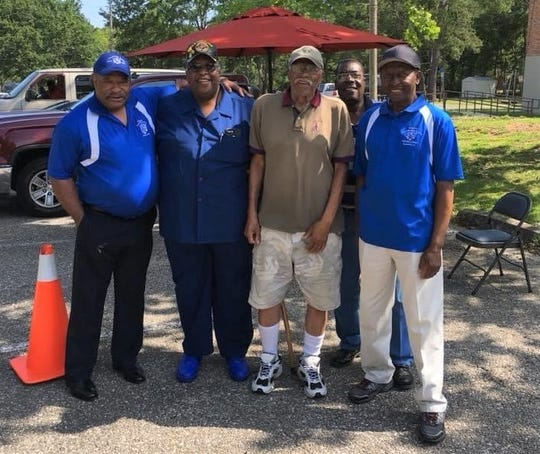 """Members of the Lincoln Varsity L Club pose with their former head coach James """"Billy"""" Oliver (brown shirt) during a reunion."""
