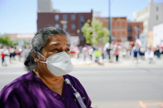 RN Irene Reyes stands across the street from the Safely Open Texas Now rally Saturday, April 25, near the El Paso County Court House in El Paso. Reyes came to observe the protest form a safe distance. Protesters demanded elected officials safely reopen the State of Texas, the County of El Paso and the city of El Paso for business.