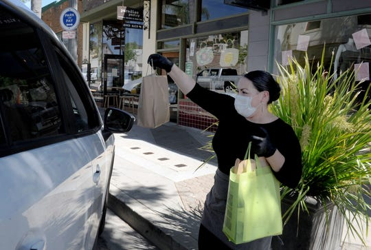 Summer Luna, a server at Paradise Pantry in Ventura, hands a bag to a curbside-delivery customer. The combination restaurant, cheese counter and wine shop is offering takeout service from its menu of salads, soups, sandwiches, imported cheeses and more.