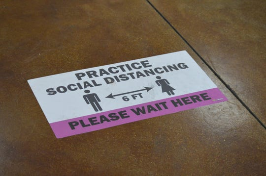 A sign at Pet Envy Grooming & Boutique in Visalia reminds pet owners to practice social distancing.