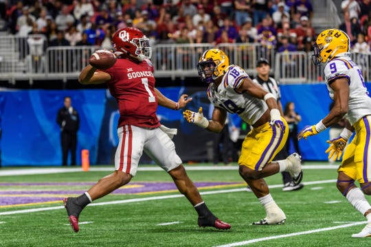 LSU linebacker K'Lavon Chaisson (18) applies pressure to Oklahoma quarterback Jalen Hurts (1) during the Peach Bowl NCAA semifinal college football playoff game, Saturday, Dec. 28, 2019, in Atlanta. (AP Photo/Danny Karnik)