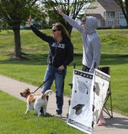Kathy Meredith and her son, Jacob (and Thumper) greet participants as high school seniors - along with some college seniors - parade Saturday through the Back Creek neighborhood near Middletown in celebration of their pending graduations. More than 50 students from about 10 schools participated in the informal recognition of their milestones.