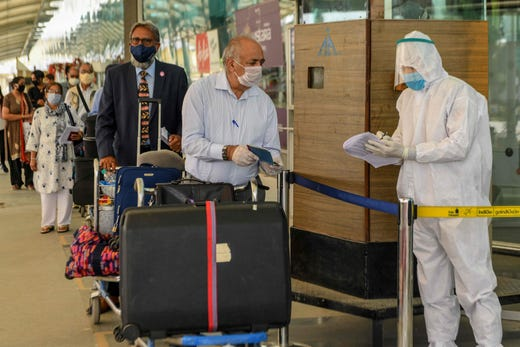 A security personnel wearing protective gear checks the passports of British nationals before check-in for a special flight to London during a government-imposed nationwide lockdown as a preventive measure against the COVID-19 coronavirus, at the Sri Guru Ram Dass Jee International Airport in Amritsar, India on April 25, 2020.