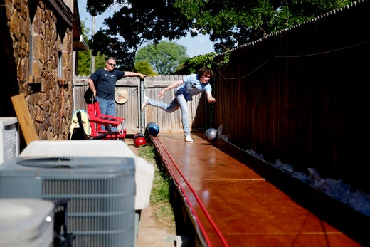 Eric Jones, 15, bowls as his dad, Heath, watches in the backyard of their Oklahoma City home, Tuesday, April 21, 2020. Health and his son Eric built a bowling lane in their backyard so that Eric, a competitive bowler, could continue to bowl while bowling alleys are closed.
