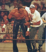 1998: Dennis Rodman drags Utah Jazz star Karl Malone across the ring during their tag team wrestling match in San Diego.