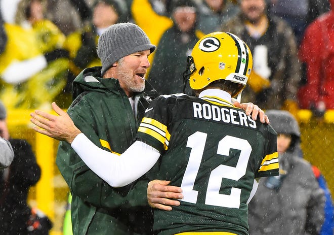 Packers quarterbacks past and present meet on the field as Brett Favre hugs Aaron Rodgers at halftime of a 2015 Thanksgiving Day game at Lambeau Field.