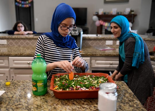 Fourteen-year-old Layan Abu-Baker, center, helps her mother, Wasan, mix the salad before breaking their fast on the second night of Ramadan, Saturday, April 25, 2020, in their home. Like many other families who are Muslim in the Coastal Bend, the Abu-Baker's adjust their traditions for the holy month because of coronavirus and social distancing.