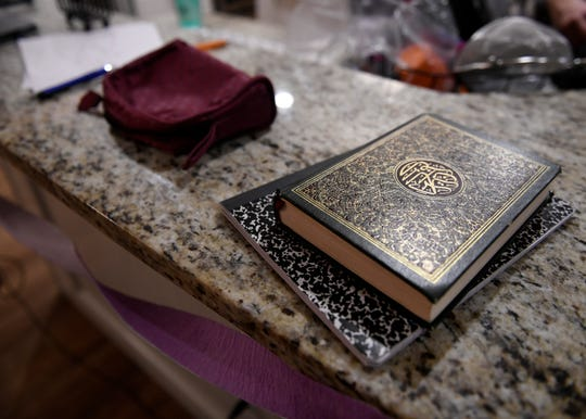 A Quran sits on a notebook on the second night of Ramadan, Saturday, April 25, 2020, in their home. Like many other families who are Muslim in the Coastal Bend, the Abu-Baker's adjust their traditions for the holy month because of coronavirus and social distancing.