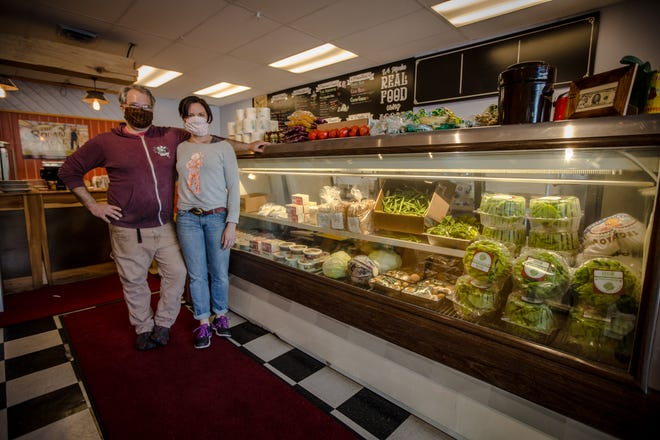 Dan and Jackie Walther don their masks for a day of selling groceries and take-out at Square Meal in Oaklyn. The cafe has converted its deli case into storage for fresh produce, dairy and other items.