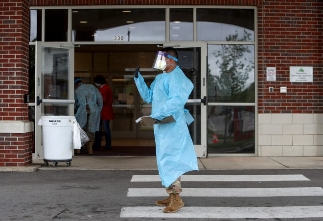 Tennessee Air and Army National Guard members of the medical task force assist Montgomery County healthcare workers at the drive thru COVID-19 coronavirus testing site at the Montgomery County Health Department in Clarksville, Tenn., on Sunday, April 26, 2020.