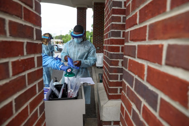 A Tennessee Air and Army National Guardsmen in the Medical Task Force slips on new gloves in between taking swabs with patients at the COVID-19 coronavirus drive-thru testing site at the Montgomery County Health Department in Clarksville, Tenn., on Sunday, April 26, 2020.