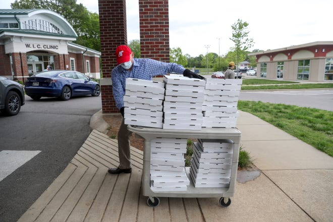 Joey Smith, Public Health Director of Clarksville-Montgomery County, tows a cart full of pizzas donated by Strawberry Alley to healthcare workers at the COVID-19 coronavirus drive-thru testing site at the Montgomery County Health Department in Clarksville, Tenn., on Sunday, April 26, 2020.