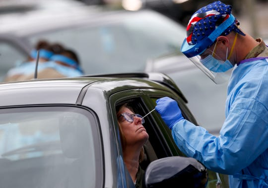 A Tennessee Air and Army National Guard Medical Task Force member administers a swab test on a patient at the COVID-19 coronavirus drive-thru testing site at the Montgomery County Health Department in Clarksville, Tenn., on Sunday, April 26, 2020.