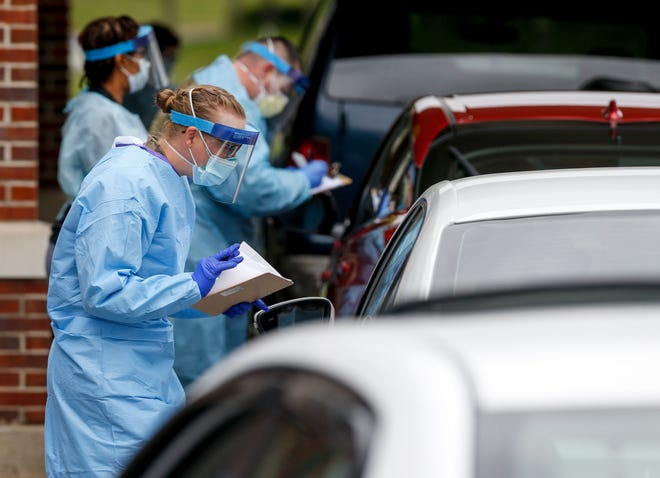 Montgomery County health care workers speak to patients in cars and fill out paperwork before a swab test at the COVID-19 drive-thru testing site at the Montgomery County Health Department in Clarksville, Tenn., on April 26, 2020.