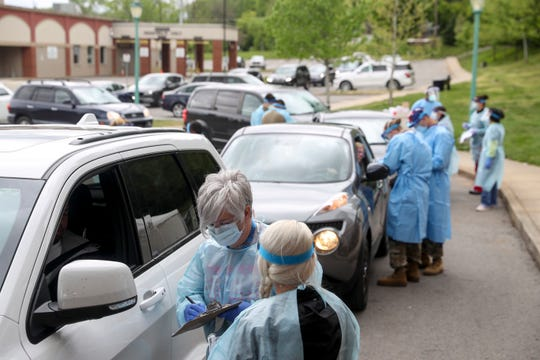 Montgomery County healthcare workers speak with patients while filling out paperwork before administering a swab test at the COVID-19 coronavirus drive-thru testing site at the Montgomery County Health Department in Clarksville, Tenn., on Sunday, April 26, 2020.