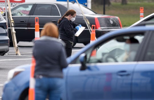Vehicles check in at the CVS drive-thru COVID-19 rapid testing site at 16301 Michigan Ave. in Dearborn, Friday, April 24, 2020.
