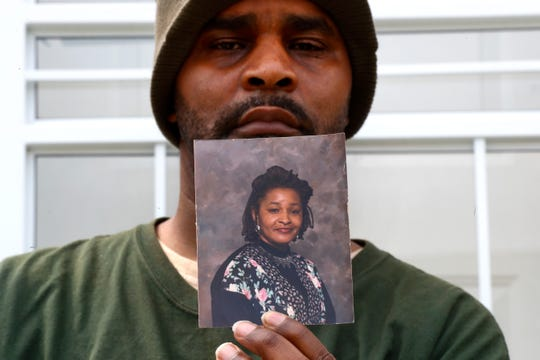 Jamon Jordan poses with a photo of his mother, Jacquelynne Jordan. Jamon Jordan could not mourn his mother in the traditional way. At Jacquelynne Jordan's memorial in early April, there were just seven people.