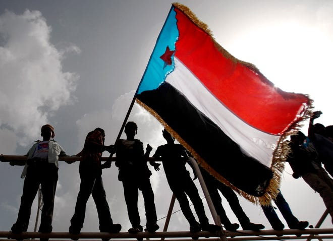 FILE - In this Jan. 13, 2013 file photo, Yemeni supporters of the Southern Separatist Movement hold a flag of the former South Yemen, during a rally in Aden, Yemen.