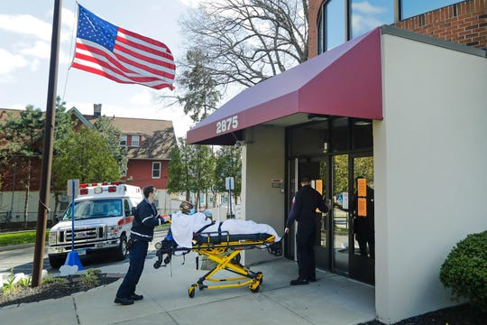Medical workers bring a patient to the Northbridge Health Care Center Wednesday in Bridgeport, Conn. To slow the spread of the coronavirus inside nursing homes, Connecticut has begun transferring infected residents to off-site recovery centers following their release from hospitals. (AP Photo/Frank Franklin II)