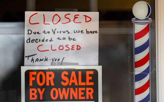 "In this April 2, 2020 file photo,  ""For Sale By Owner"" and ""Closed Due to Virus"" signs are displayed in the window of a store in Grosse Pointe Woods. Business filings under Chapter 11 of the federal bankruptcy law rose sharply in March, and attorneys who work with struggling companies are seeing signs that more owners are contemplating the possibility of bankruptcy. Government aid my simply be too little too late. (AP Photo/Paul Sancya)"