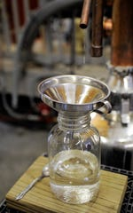 "The ""heads"" from a batch of distilling spirits drip into a jar at Dusty Barn Distillery on Thursday, Apr. 23, 2020."