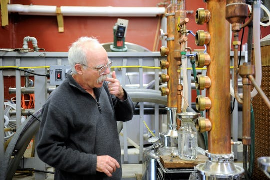 Dr. Duane Kuhlenschmidt samples a trickle of drinkable alcohol flowing out of a condenser at Dusty Barn Distillery on Thursday, Apr. 23, 2020.