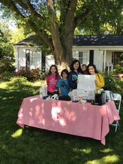 Farah Apicella and children Avery, Micah, Ezra and Rori served donuts and coffee to neighbors harder hit by the storm that tore through their Botany Woods area neighborhood. April 26, 2020