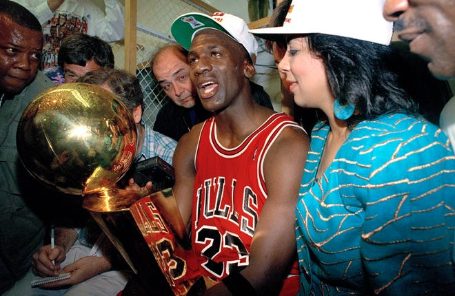 Chicago Bulls Michael Jordan holds the trophy after the Bulls 108-101 win over the Los Angeles Lakers in game five for the NBA championship in Inglewood, California, June 12, 1991. (AP Photo/Reed Saxon)