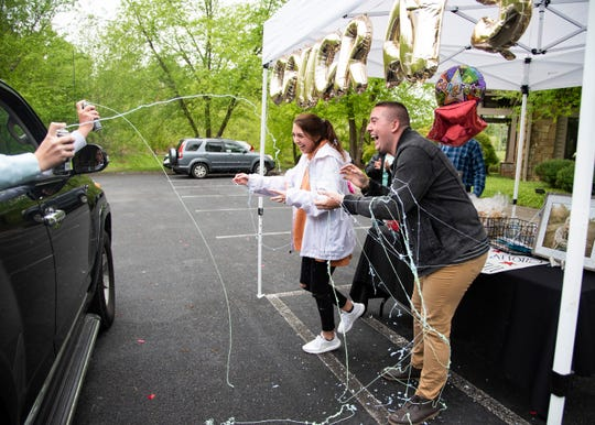 Twins Austin and Abby Angel get sprayed with Silly String at their drive-through graduation party outside the Timberlake Clubhouse in Knoxville, Tenn., on Sunday, April 26, 2020. Knox County's high schools have postponed their 2020 graduation ceremonies until further notice as a result of the coronavirus pandemic.
