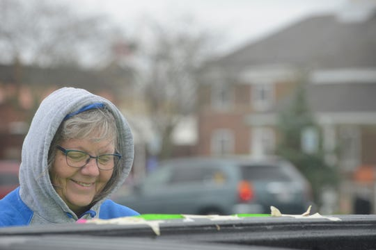 Dorcas Schreck, an intervention specialist for kindergarten and first grade at Crestline Schools,  tapes a sign to the back of her truck.