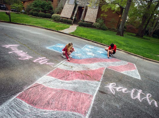 Layne Bjornseth, left, and her boyfriend Ben Glover touch up a street mural with chalk off Southampton Court in Decatur, Ala., on Monday, March 30.
