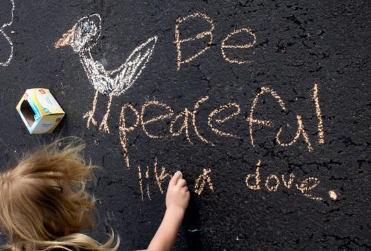 Amber Dodd, 7, makes chalk art with  uplifting messages on her driveway in Salem, Va., on Wednesday, March 8. Residents have have been making chalk drawings on their driveways to connect with one another.