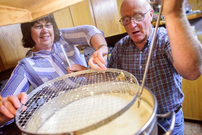 In this Sept. 20, 2017, file photo, Shari, left, and Dane Lambson pull out a curd cutter from a large pot of curdled milk at their home in Ramah, N.M. The COVID-19 pandemic is choking New Mexico's dairy market, forcing many farmers to throw surplus milk into irrigation ponds.
