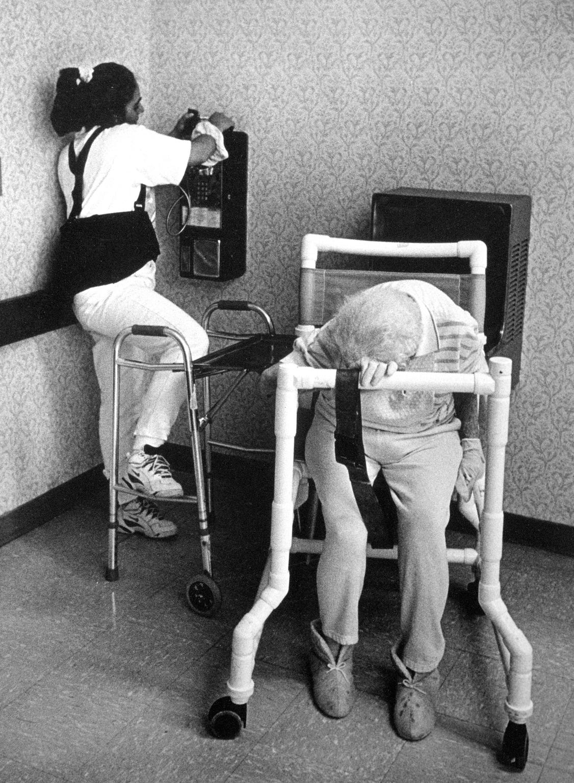 An aide in a nursing home facility in Los Alamos makes a call while a resident sleeps on her walker, 2002.