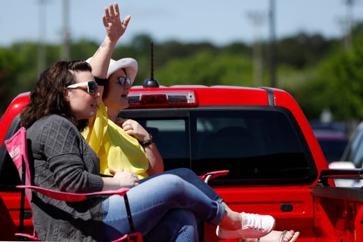 Members of the congregation worship from the back of a pickup truck during an outdoor church service at Cornerstone Church in Athens, Ga, on Sunday, April 26, 2020.